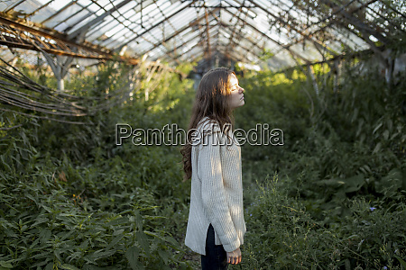 young woman in abandoned greenhouse