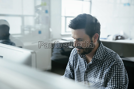 bearded man behind window in office