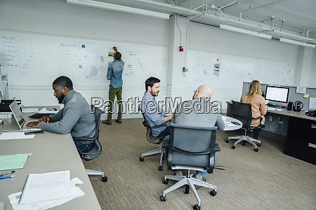 workers in office with whiteboard