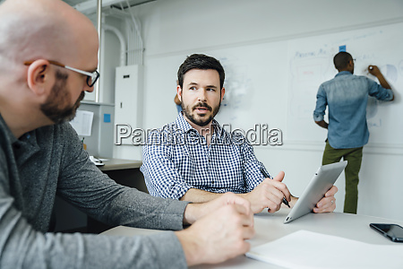 men using digital tablet during meeting