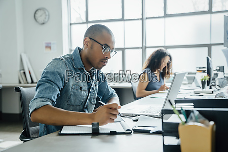 man holding pen using laptop in
