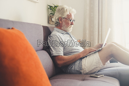 senior man using laptop on sofa