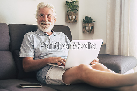 smiling senior man using laptop on