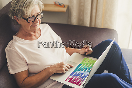 senior woman using laptop on sofa