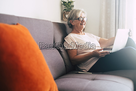 smiling senior woman using laptop on