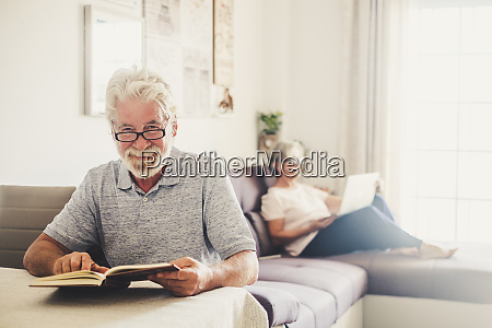 senior man reading book as his