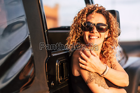 smiling woman wearing sunglasses with arm