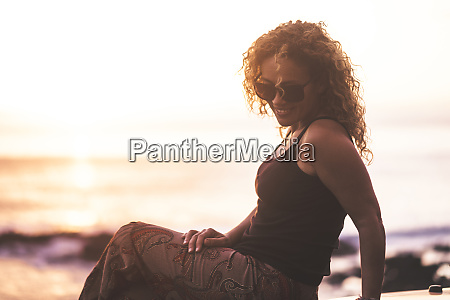 smiling woman sitting by beach at