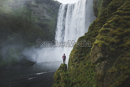 man standing by skogafoss waterfall in
