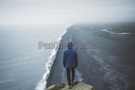 man wearing blue coat above beach