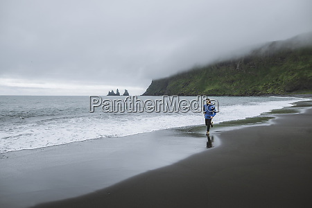 man jogging on beach in vik