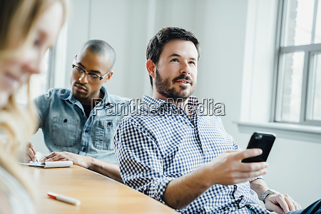 man holding smart phone during meeting