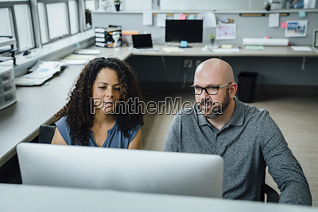 coworkers using computer in office