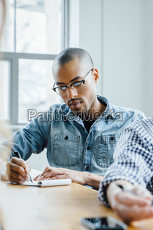 man using note pad during meeting