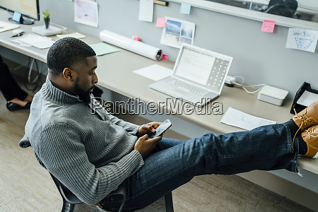 man with his feet up using