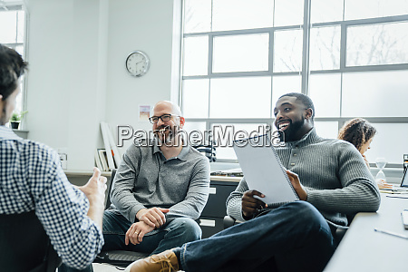 men smiling during meeting in office
