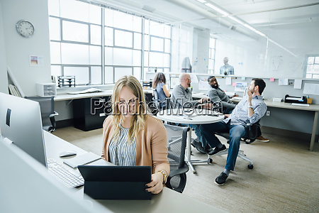 woman using digital tablet in office