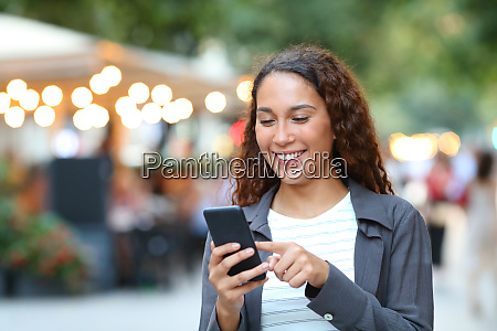 happy mixed race woman using smart