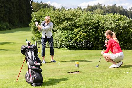 male golfer putting golf ball on