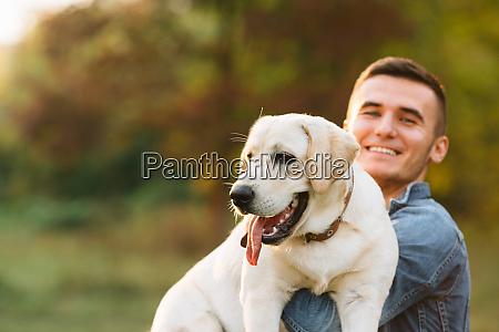 smiling man with his dog labrador