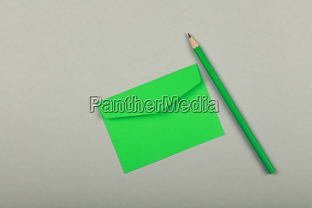 closed green paper envelope over grey