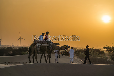 people riding with camels in the
