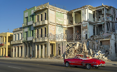 an old car passes the demolished