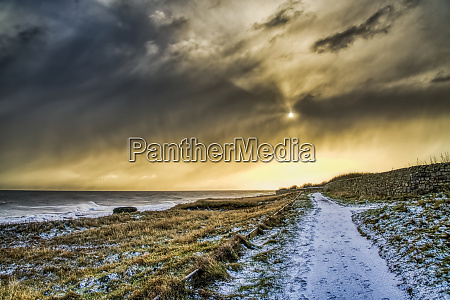 snow covered path along the coastline