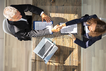 male manager shaking hands with female