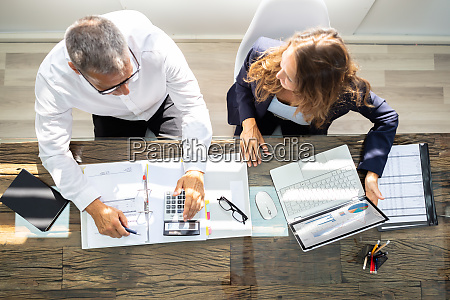 businesspeople using laptop in office