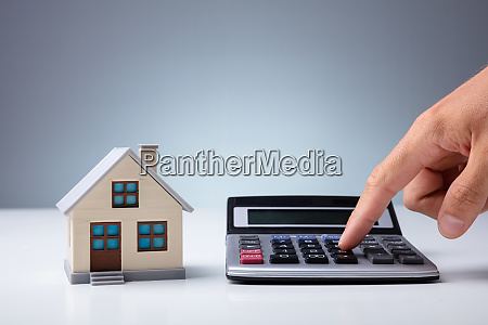 person using calculator near house model