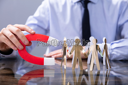 businessperson attracting leads with horseshoe magnet