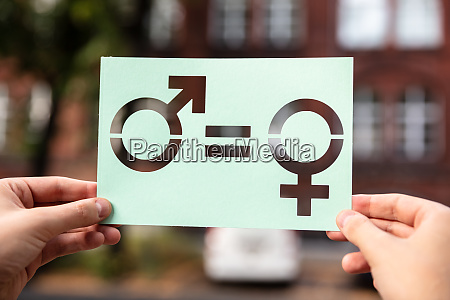 hands holding paper with cutout gender