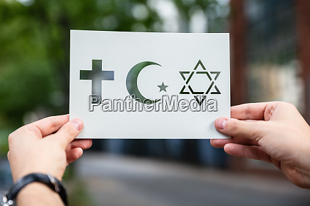 hands holding paper with cutout religion
