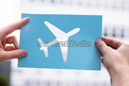 hands holding paper with cutout airplane