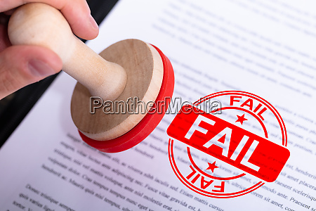 businessman putting fail stamp on document