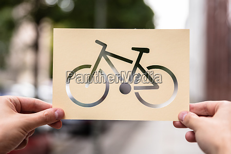 hands holding paper with cutout bicycle