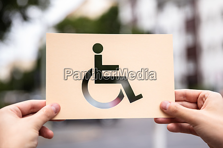 hands holding paper with cutout disabled