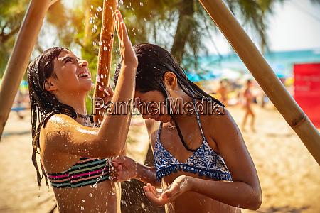 kids playing under beach shower