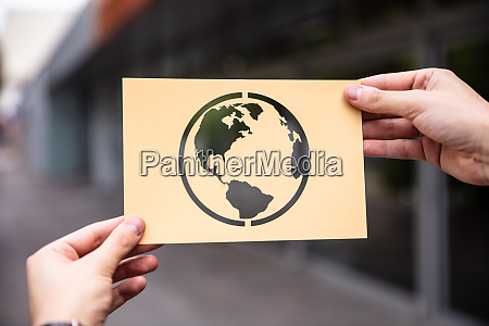 hands holding paper with cutout planet
