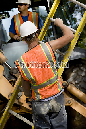 two construction workers with heavy equipment