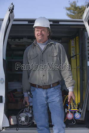 plumber holding refrigerant pumps and gauges