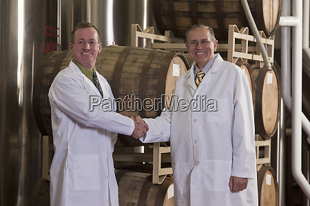 two scientists shaking hands in a