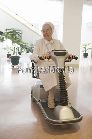 nun riding a motorized wheelchair