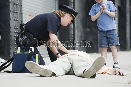 woman police officer administering first aid