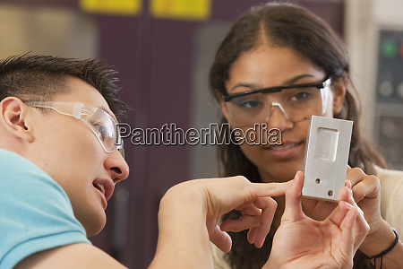 engineering students examining a machined part