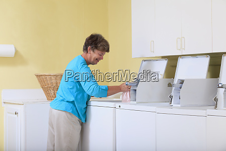 senior woman putting laundry in a