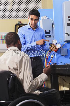 students discussing air conditioner recharging gauging