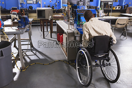 student in wheelchair studying furnace electronic
