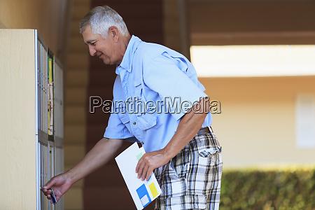 senior man checking his mailbox